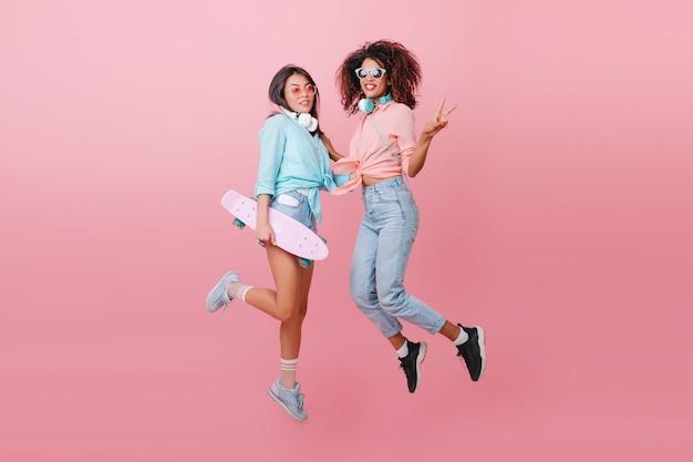 Un ritratto integrale di due signore sportive che saltano e che sorridono. affascinante ragazza pattinatrice in camicia blu divertendosi con un'amica africana in scarpe nere. Foto Gratuite