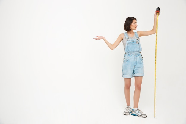 Full length portrait of woman measure herself with tape Free Photo