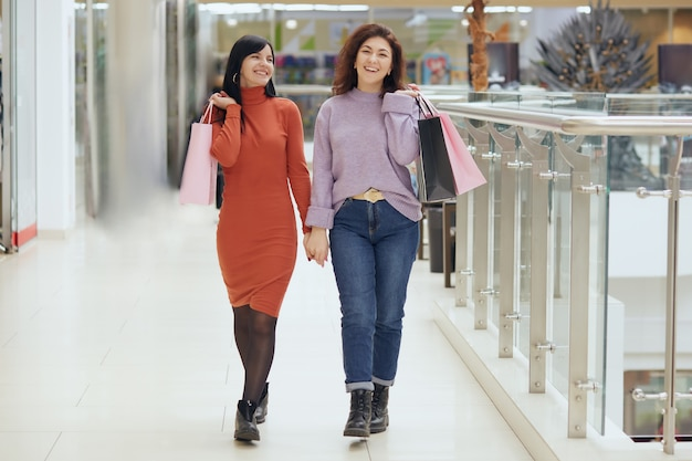 Full length portrait of young females posing in mall with shopping bags, women wearing casual attires Premium Photo