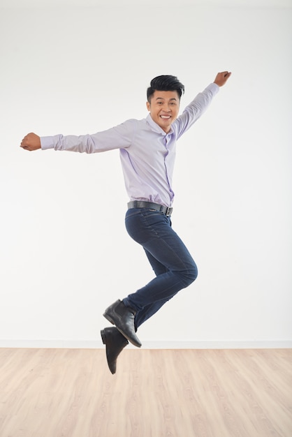 Full length portrait of young man jumping full of happiness Free Photo
