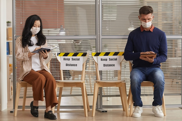 Full length portrait of young people wearing masks while waiting in line in office with keep social distance signs, copy space Premium Photo