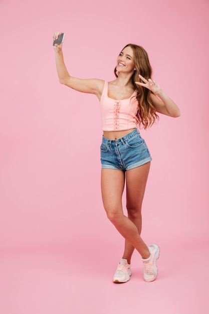 Full length portrait of young smiling readhead woman in summer wear makes selfie on smartphone, showing peace sign Free Photo