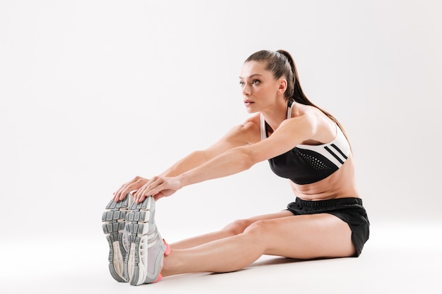 Full length portrait of a young sportwoman stretching muscles Free Photo