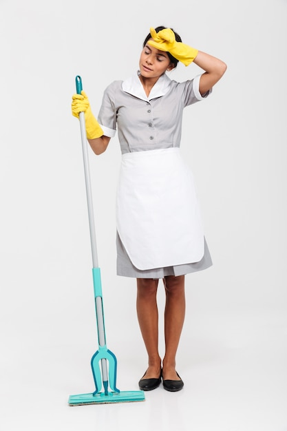 Full length portrait of young tired woman in uniform holding mop and wipes sweat from her forehead Free Photo
