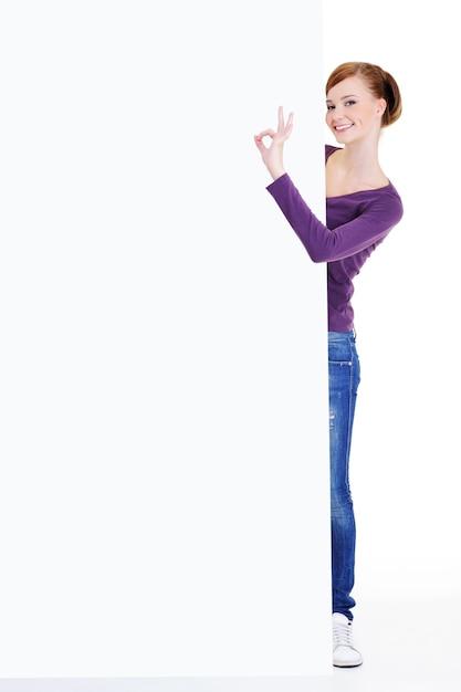 Il ritratto integrale di una giovane donna osserva fuori a causa del tabellone per le affissioni di pubblicità con il gesto giusto Foto Gratuite