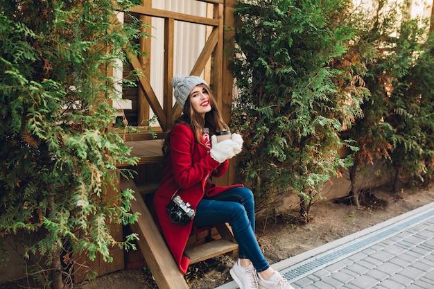 赤いコート、ニット帽子、屋外の緑の枝の間の木製の階段の上に座っている白い手袋で完全な長さのかわいい女の子。彼女はコーヒーを持ち歩き、笑っています。 無料写真
