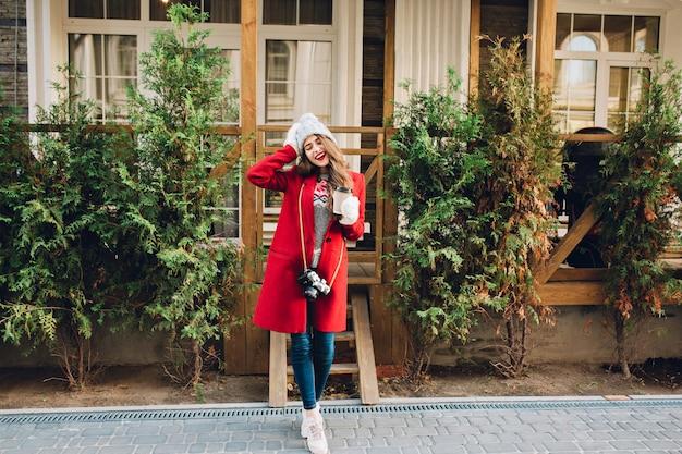 赤いコートの長い髪と木造住宅の上にニット帽子立って全長美少女。彼女はカメラとコーヒーを持って白い手袋をします。目を閉じて満足そうです。 無料写真
