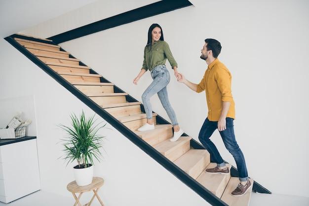 전체 길이 프로필 잘 생긴 남자와 그의 예쁜 아가씨가 새로운 현대 아파트에서 위층으로 올라가고 있습니다. 프리미엄 사진
