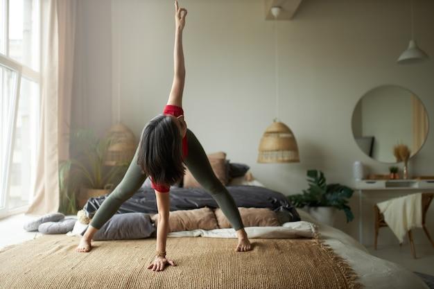 Colpo integrale di giovane donna a piedi nudi con corpo atletico flessibile in piedi sul tappeto in parivrtta prasarita padottanasana, facendo yoga twist, migliorando la digestione, rafforzando i muscoli posteriori della coscia e le cosce Foto Gratuite