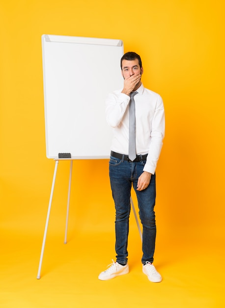 Full-length shot of businessman giving a presentation on white board over isolated yellow background covering mouth with hands Premium Photo