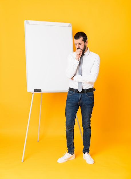 Full-length shot of businessman giving a presentation on white board over isolated yellow background is suffering with cough and feeling bad Premium Photo