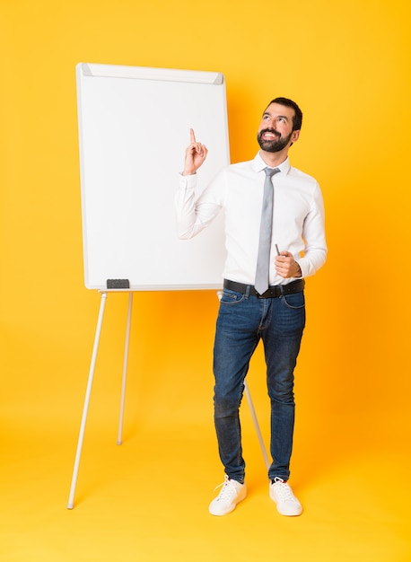 Full-length shot of businessman giving a presentation on white board over isolated yellow background pointing up and surprised Premium Photo