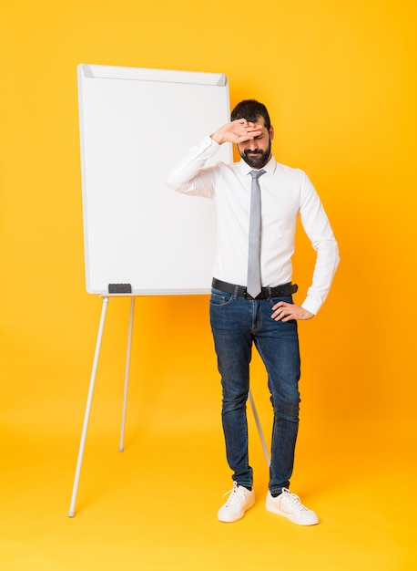 Full-length shot of businessman giving a presentation on white board over isolated yellow background with tired and sick expression Premium Photo