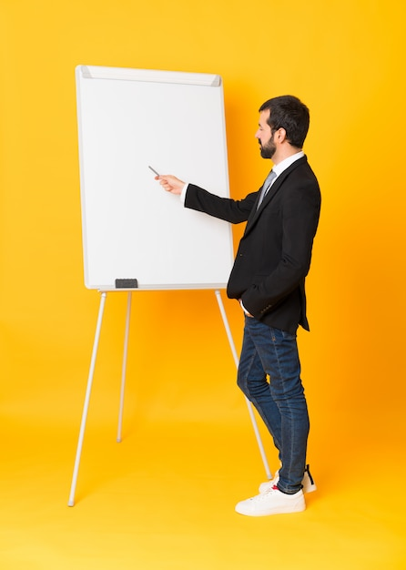Full-length shot of businessman giving a presentation on white board over isolated yellow background Premium Photo