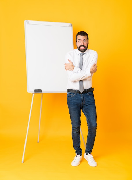 Full-length shot of businessman giving a presentation on white board over isolated yellow freezing Premium Photo
