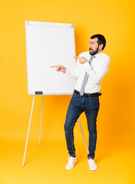 Full-length shot of businessman giving a presentation on white board over isolated yellow frightened and pointing to the side Premium Photo