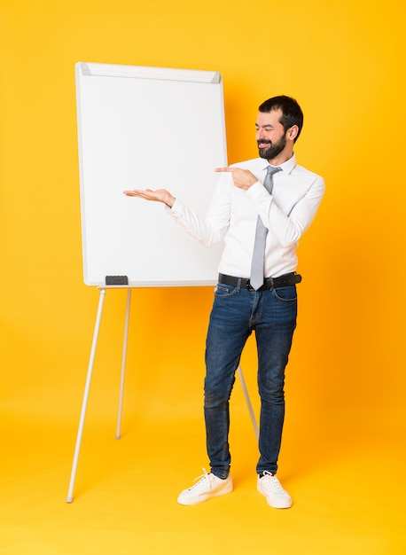 Full-length shot of businessman giving a presentation on white board over isolated yellow holding copyspace imaginary on the palm to insert an ad Premium Photo