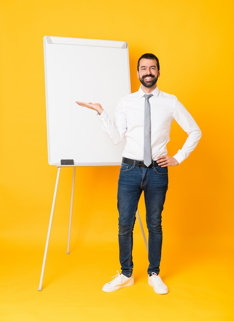 Full-length shot of businessman giving a presentation on white board over isolated yellow holding copyspace imaginary on the palm Premium Photo