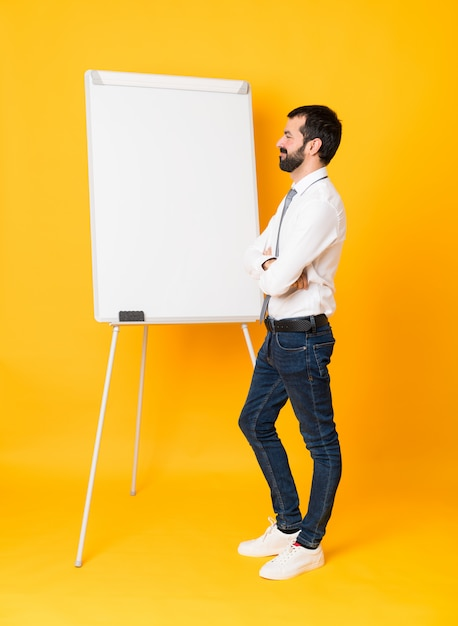 Full-length shot of businessman giving a presentation on white board over isolated yellow in lateral position Premium Photo