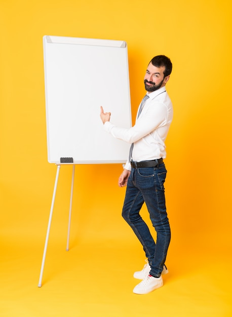 Full-length shot of businessman giving a presentation on white board over isolated yellow pointing back Premium Photo