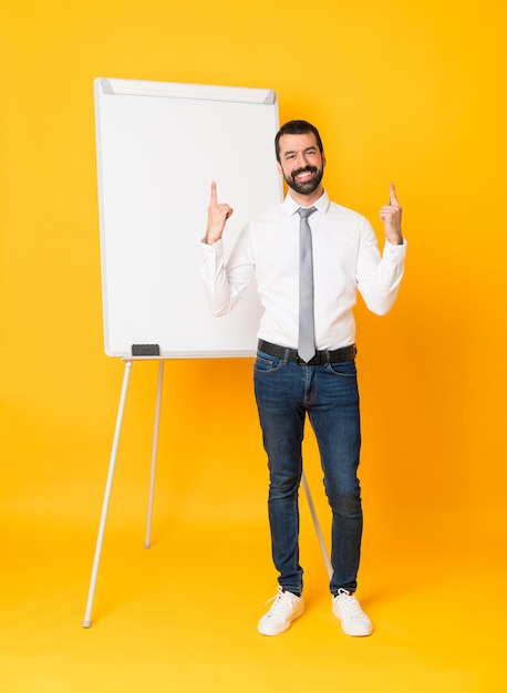 Full-length shot of businessman giving a presentation on white board over isolated yellow pointing up a great idea Premium Photo