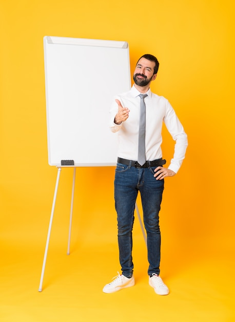 Full-length shot of businessman giving a presentation on white board over isolated yellow shaking hands for closing a good deal Premium Photo