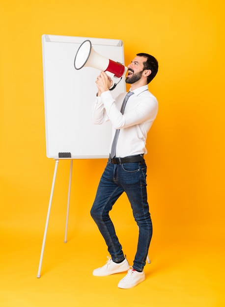 Full-length shot of businessman giving a presentation on white board over isolated yellow shouting through a megaphone Premium Photo