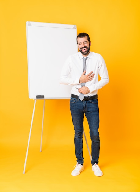 Full-length shot of businessman giving a presentation on white board over isolated yellow smiling a lot Premium Photo