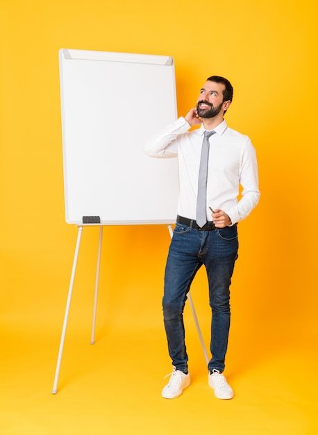 Full-length shot of businessman giving a presentation on white board over isolated yellow thinking an idea Premium Photo