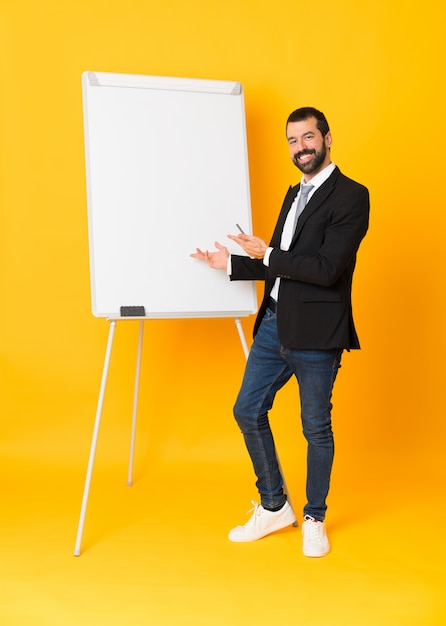 Full-length shot of businessman giving a presentation on white board over isolated yellow Premium Photo