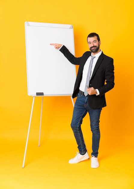 Full-length shot of businessman giving a presentation on white board over yellow Premium Photo