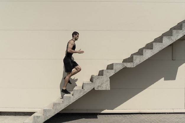 Full length shot of healthy athletic man climbing up on stairs. Free Photo
