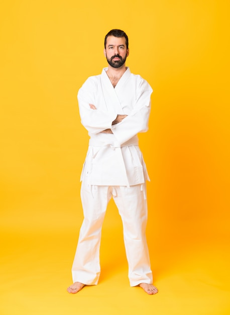 Full-length shot of man over isolated yellow background doing karate keeping the arms crossed Premium Photo