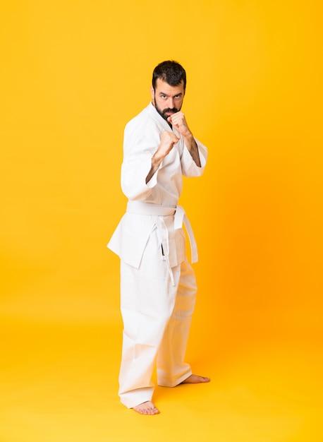 Full-length shot of man over isolated yellow doing karate Premium Photo