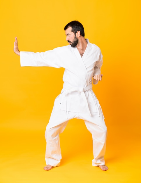 Full-length shot of man over isolated yellow  doing karate Premium Photo