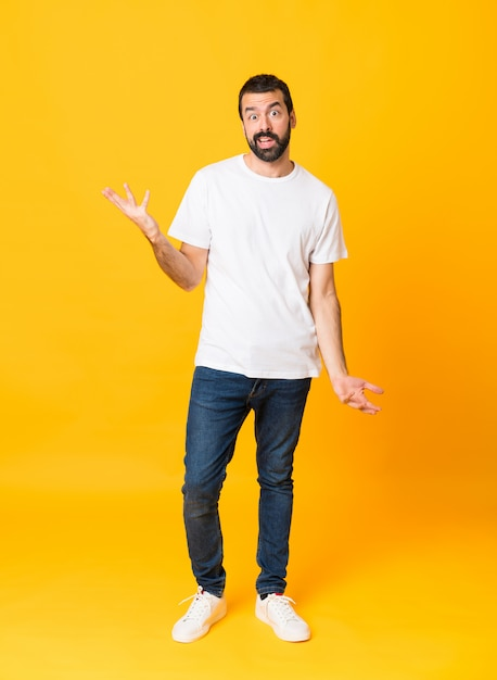 Full-length shot of man with beard over isolated yellow making doubts gesture Premium Photo