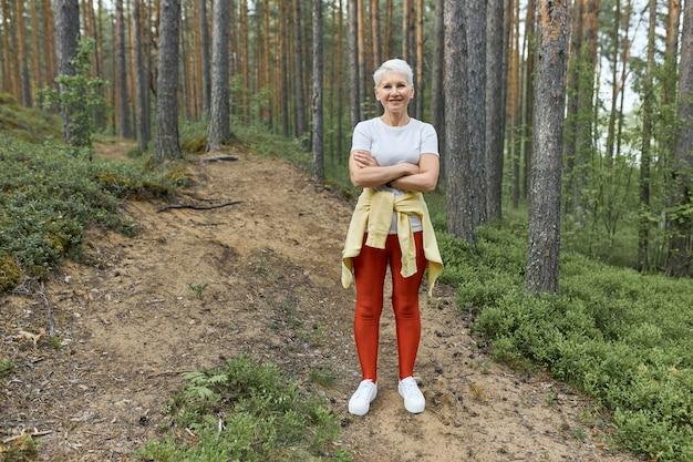 Снимок в полный рост активной зрелой женщины со светлыми волосами и подтянутым телом, стоящей на тропе в лесу в спортивной одежде, отдыхающей во время тренировки, скрестив руки. люди, активность и возраст Бесплатные Фотографии