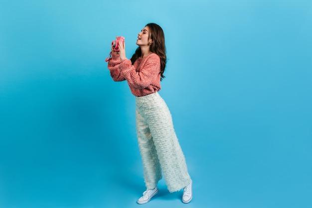 白いズボンとピンクのセーターで魅力的なブルネットのフルレングスのショット。興味のある女の子がinstaxで写真を撮ります。 無料写真