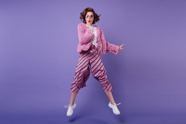 보라색 벽에 점프 스트라이프 바지에 기쁜 곱슬 여자의 전체 길이 샷. 장난하는 선글라스에 멋진 여자의 실내 초상화. 무료 사진