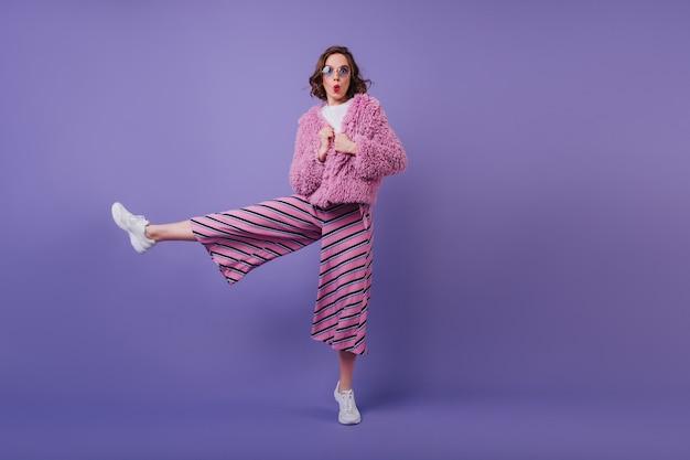 Кадр в полный рост вдохновленной темноволосой девушки, стоящей на одной ноге. кавказская женщина выражает изумление, позируя с выражением лица поцелуя на фиолетовой стене. Бесплатные Фотографии