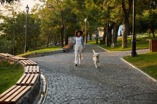 Полнометражный снимок довольно здоровой молодой леди, идущей утром в парке с собакой Бесплатные Фотографии
