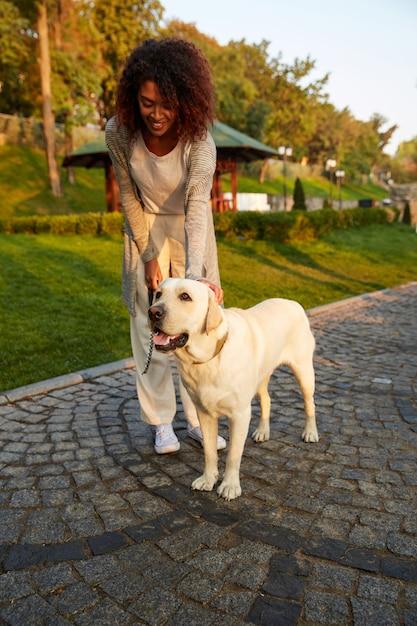 犬と一緒に公園で朝歩いているかなり健康な若い女性の全身ショット 無料写真