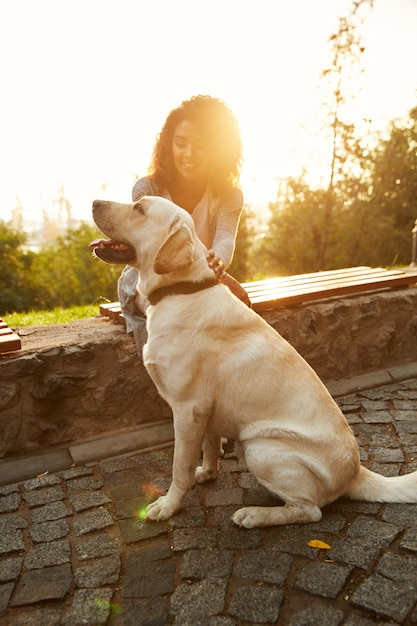 Полнометражный снимок довольно белая собака с владельцем в парке, прогулки Бесплатные Фотографии