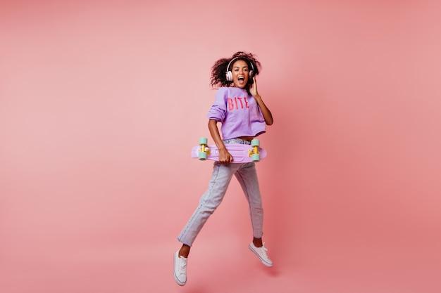 Снимок в полный рост потрясающей черной женщины в стильных джинсах, прыгающей на розовом. кудрявая африканская девушка со скейтбордом, выражая положительные эмоции. Бесплатные Фотографии