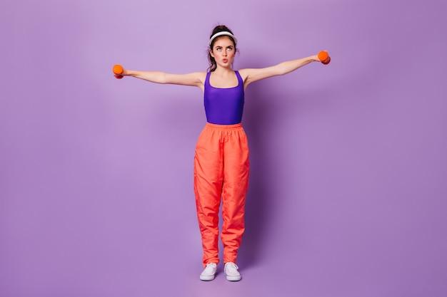 Снимок в полный рост женщины в широких спортивных штанах и кепке, делающей упражнения для рук с гантелями на сиреневой стене Бесплатные Фотографии