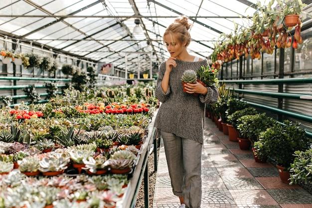 Colpo integrale di donna bionda premurosa in pantaloni grigi e maglione che cammina attraverso la serra. Foto Gratuite
