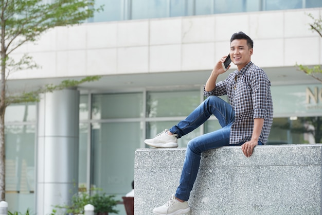 Full-length shot of young asian guy sitting on marble outdoors talking on the phone Free Photo