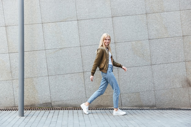Full-length shot of young woman walking in the street Free Photo