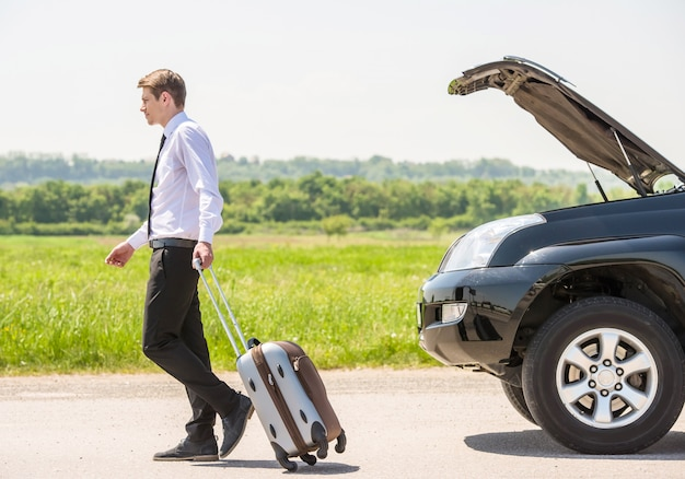 Full length side view of young businessman with suitcase. Premium Photo