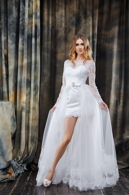 Full length studio portrait of beautiful bride in short wedding dress Premium Photo